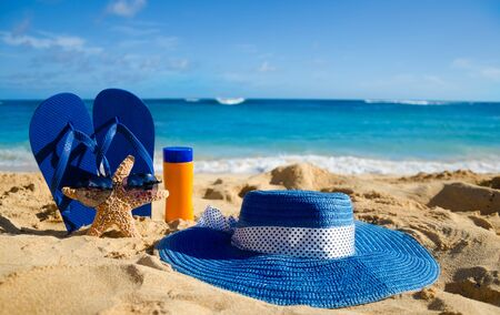 Blue Flip flops, sunscreen, womans summer hat and starfish with sunglasses on sandy beach in Hawaii, Kauai photo