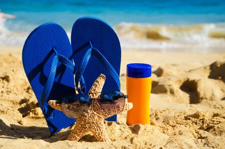 Blue Flip flops, sunscreen and starfish with sunglasses on sandy beach in Hawaii, Kauai photo