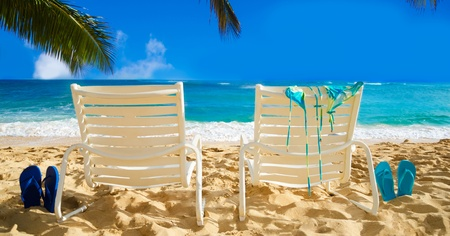 Two white beach chairs under palm leaves by the ocean, with bikini and flip flops.