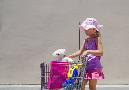 northridge: Girl with toys in shopping bag in kids shopping cart  Note - this typical white bear was made by hands of my daughter on Build-A-Bear Workshop in Northridge, California, USA.