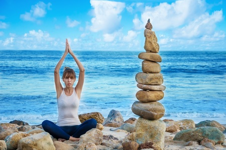 Young pretty woman practicing yoga on the beach by the ocean  photo