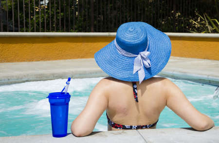 Girl in summer hat relaxing in jacuzzi (hot tub)
