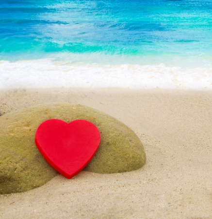 Red Heart shape on the sandy beach by the ocean Stock Photo