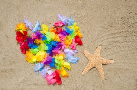 Heart shape of the Hawaiian flowers and starfish on the beach photo