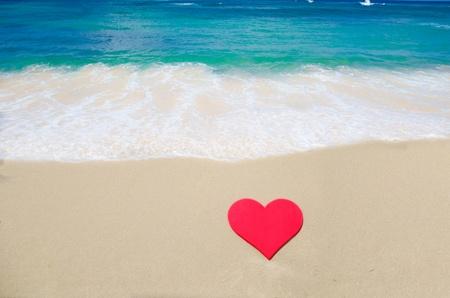 Heart shape on sandy beach by the ocean photo