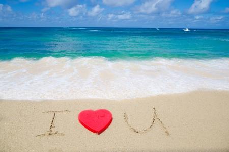 """i love u: Signe """"I Love U"""" avec forme de coeur rouge sur la plage Banque d'images"""