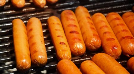 Sausages preparing on grill in summer day Stock Photo