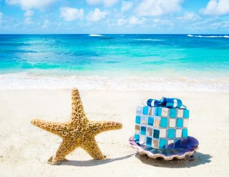 Starfish en zeeschelp met kerstversiering op zandig strand in zonnige dag-concept vakantie