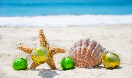 Starfish and seashell with Christmas balls on sandy beach in sunny day- holiday concept