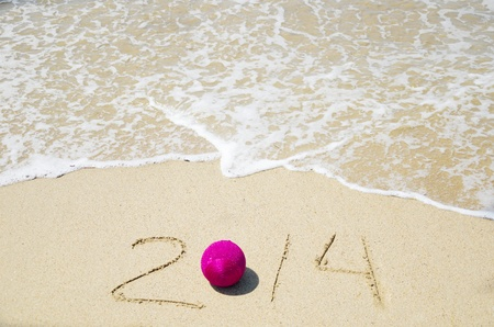 Number 2014 with christmas decoration on the sandy beach - holiday concept Stock Photo - 21394232