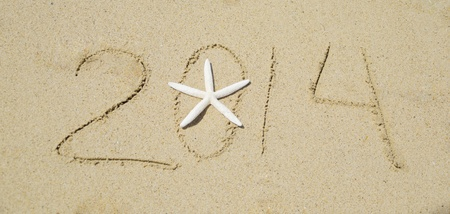 Number 2014 with starfish on the sandy beach - holiday concept Stock Photo - 21394234