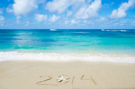 Number 2014 with starfish on the sandy beach - holiday concept