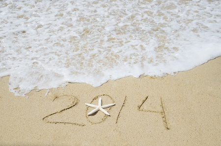 Number 2014 with starfish on the sandy beach Stock Photo - 21394236