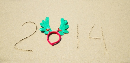 Number 2014 with christmas decoration on the sandy beach Stock Photo - 21394246