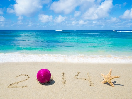 Number 2014 with christmas ball and starfish on the sandy beach