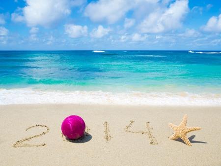 Nummer 2014 met kerst bal en zeester op het strand Stockfoto