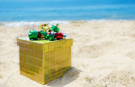 caja navidad: Caja de regalo de oro en la playa de arena en el soleado d�a de concepto de las vacaciones
