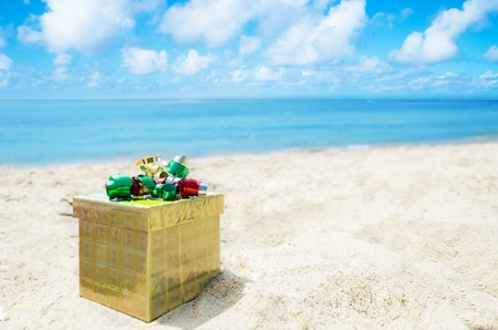 Gold Gift box on sandy beach in sunny day- holiday concept Stock Photo - 21395517