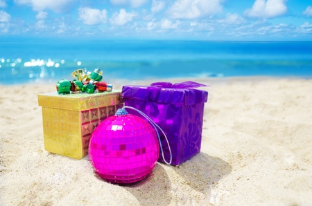 Two gift boxes Christmas ball on sandy beach in sunny day- holiday concept photo