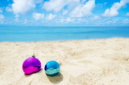 Two Christmas balls on sandy beach in sunny day- holiday concept