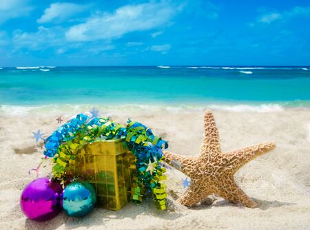 Starfish with gift box and Christmas balls on sandy beach in sunny day- holiday concept Stock Photo - 21395524