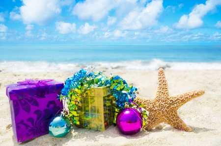 christmas concept: Starfish with two gift boxes and Christmas balls on sandy beach in sunny day- holiday concept Stock Photo