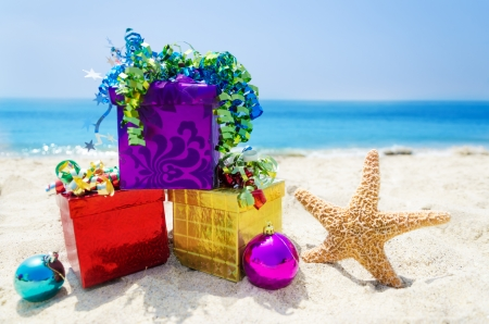 Starfish with Christmas balls and three gift boxes on sandy beach in sunny day- holiday concept Stock Photo - 21598648