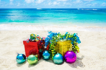 Two gift boxes with Christmas balls on sandy beach in sunny day- holiday concept photo