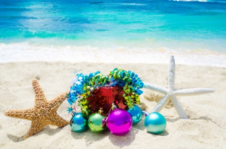 tropical christmas: Two Starfishes with Christmas balls and gift box on sandy beach in sunny day- holiday concept