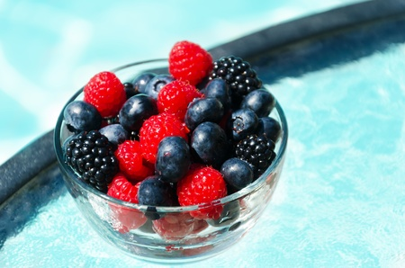 Fresh berries by the swimming pool in sunny morning