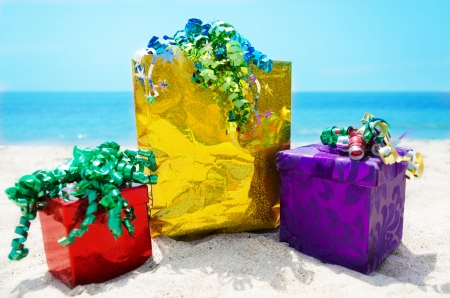 Gold gift bag and two gift boxes on sandy beach in sunny day- holiday concept Stock Photo - 21598590