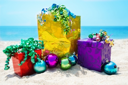 Gold gift bag and two gift boxes with Christmas balls on sandy beach in sunny day- holiday concept Stock Photo - 21598591