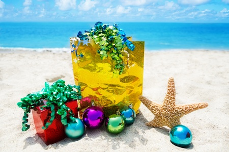 Starfish with gift box and bag and christmas balls on sandy beach in sunny day- holiday concept