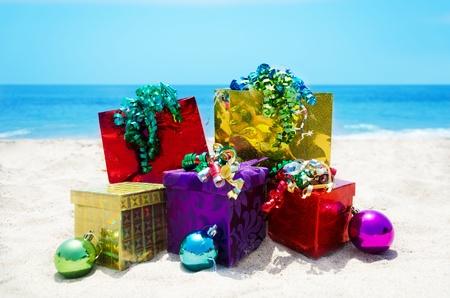 three gift boxes: Tres cajas de regalo y dos bolsas de regalo con las bolas de los christmass en la playa de arena en el soleado d�a el concepto de las vacaciones