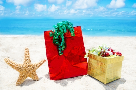 Starfish with gift box and bag on sandy beach in sunny day- holiday concept photo