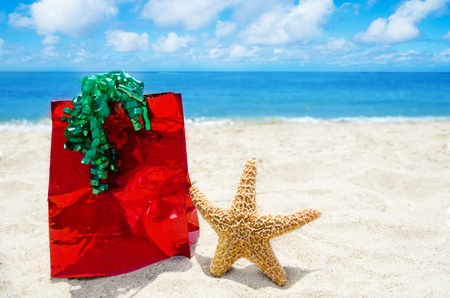 Starfish with red gift bag on sandy beach in sunny day- holiday concept photo