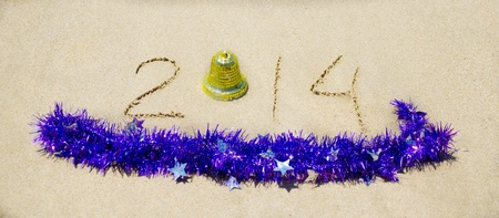 Number 2014 with christmas decorations on the sandy beach - holiday concept Stock Photo - 21785658