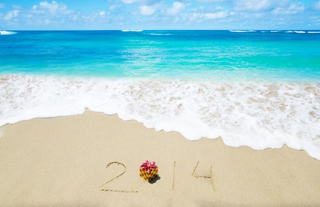 Number 2014 with christmas decoration on the sandy beach - holiday concept Stock Photo - 21785660