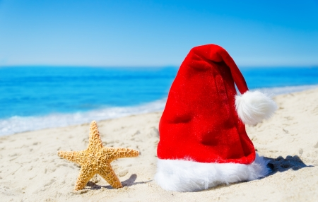 Christmas hat with starfish on the beach by the ocean - holiday concept