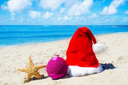 Christmas hat with christmas ball and starfish on the beach by the ocean - holiday concept Stock Photo