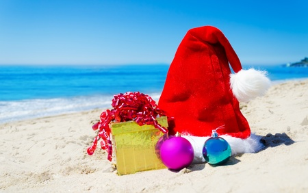 Christmas hat with gift box and christmas balls on the beach by the ocean - holiday concept photo