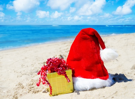 Christmas hat with gift box on the beach by the ocean - holiday concept photo