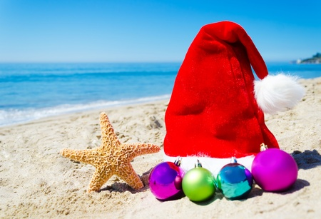 Starfish with christmas hat and balls on the beach by the ocean - holiday concept