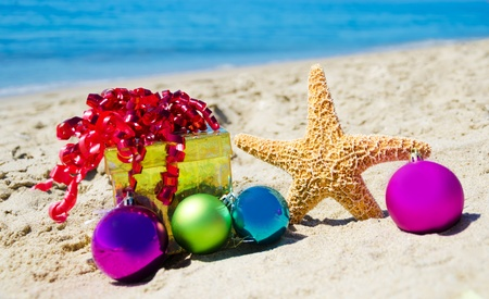 Starfish with gift box and christmas balls on the beach by the ocean - holiday concept Stock Photo - 21962573