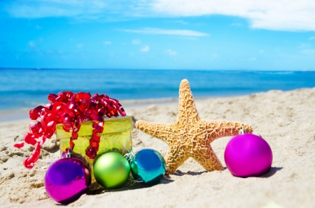 휴가 개념 - 바다로 선물 상자 및 해변에서 크리스마스 공 불가사리