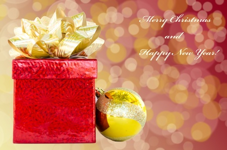Gift box and Christmas ball on holiday's background with sign 'Merry Christmas and Happy New Year!' photo