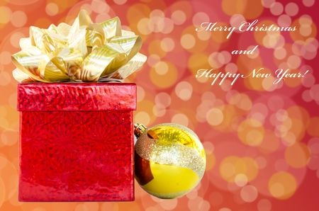 Gift box and Christmas ball on holidays background with sign Merry Christmas and Happy New Year! photo
