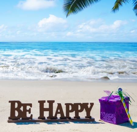 Sign Be Happy with Birthday decorations on the sandy beach by the ocean photo