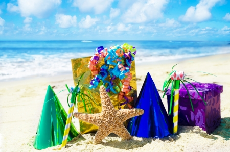 noisemaker: Starfish with Birthday decorations on the sandy beach by the ocean Stock Photo