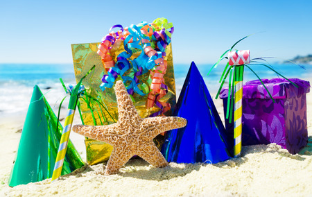 Starfish with Birthday decorations on the sandy beach by the ocean photo
